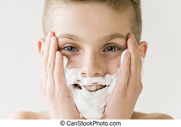 Smiling Young Boy Applying Shaving Cream to Face - Close Up...