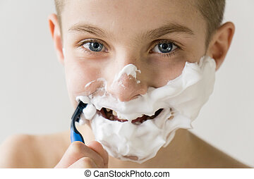 Smiling Boy Shaving Face with Plastic Razor - Head and...