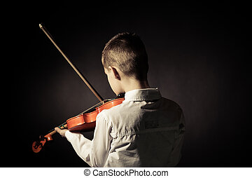 Rear view of child playing violin in darkened room - Rear...