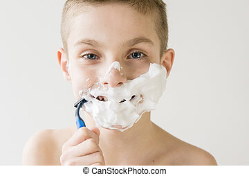 Excited Young Boy Shaving with Plastic Razor - Head and...
