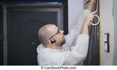 Worker protecting batten moulding with masking tape before painting at home improvement work.