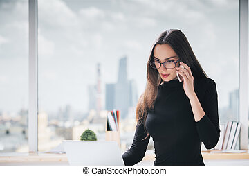 Woman on phone using laptop - Portrait of attractive young...