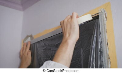 Worker protecting batten moulding with masking tape before...