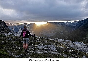Woman watching sunset in mountains. - Lake Ann trail in...