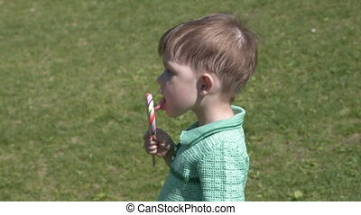 Child with lollipop outdoor - Little boy eating sweet...