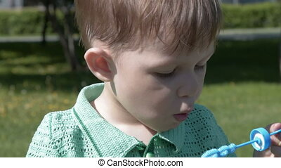 Child blowing bubbles outdoor