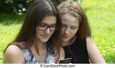 Cheerful teenager girls with mobile in the park - Smiling...