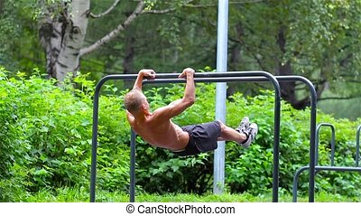 Athletic man doing gymnastics elements on bars in City Park...