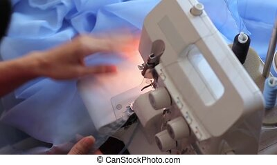 Woman corrects and processes the fabric on the overlock. Diligent, hard work. Close-up.