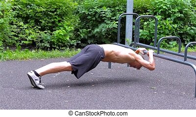 Athletic man doing push ups in City Park side view Workout...