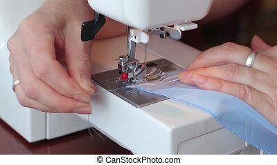 The woman begins to sew on the sewing machine. Women's hands. Close-up.