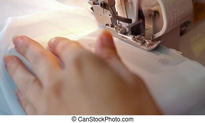 Woman treated tissue using overlock. Overlock foot closeup. Women's hands. Sewing machine.