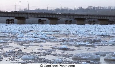 Spring break, floating, drifting, ice on the river against the background of the road bridge view from the shore.