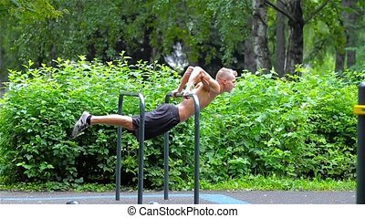 Athletic man doing pushups on bars in City Park. side view. Workout.