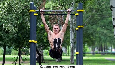 Athletic man doing lifting legs on horizontal bar in City...