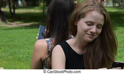 Teens spending leisure with cells - Two teenager girls...