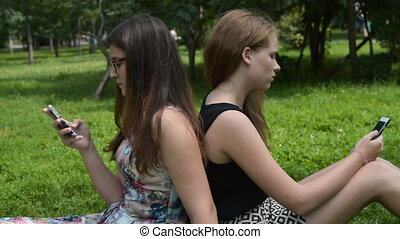 Teen girls with cellphones in the park - Teenager girls...