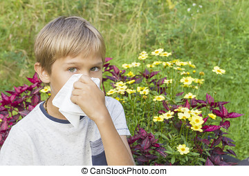 Child is blowing his nose. Flowers and green meadow behind him. Healthcare, medicine, allergy concept.