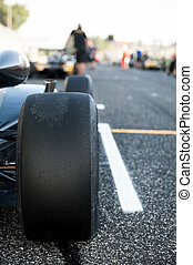 Black slick motor sport car tire close up