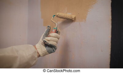 working with roller Hand paints the wall in orange color....