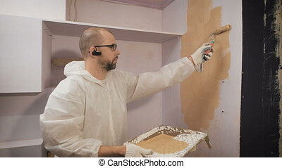 Repair of houses with their own hands. Man causes the paint...