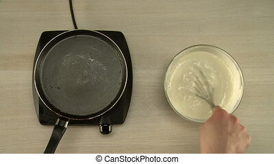 First-person view on chef cooks dough for pancakes -...