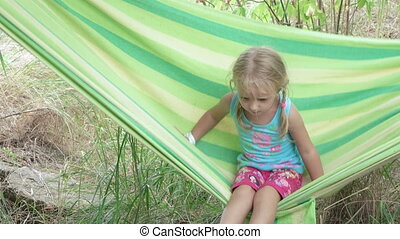 Little Girl on nature - Child riding in hammock on nature