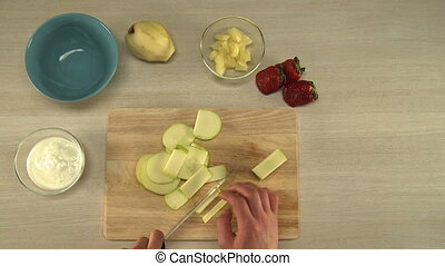 View on chef cutting apple for fruit salad - First-person...