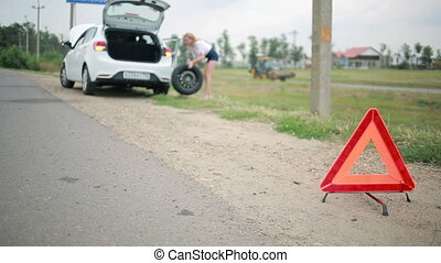 Girl changing a punctured tire at the car. repair of cars on...