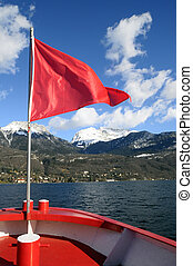 Annecy Lake and mountains from boat and red flag