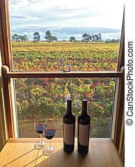 Glass of red wine next to bottles near windows with soft...