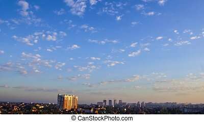 Timelapse movie of morning sky with white spindrift clouds above the city