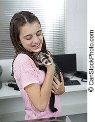 Girl Holding Weasel In Veterinary - Happy little girl...