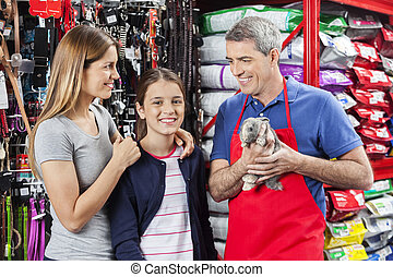 Happy Family Standing With Salesman Holding Rabbit At Store...