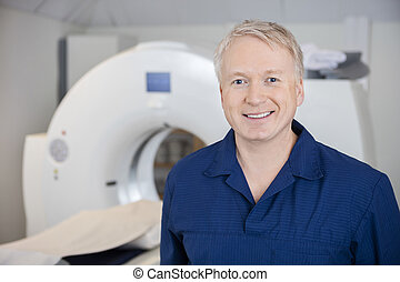 Professional Standing By MRI Machine In Clinic - Smiling...