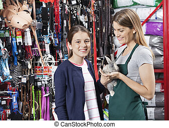 Happy Girl Standing With Saleswoman Holding Rabbit At Store...