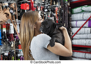 Loving Mid Adult Woman Carrying French Bulldog - Side view...