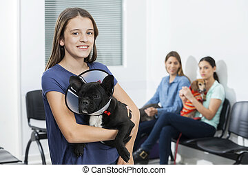 Girl Holding French Bulldog With Cone In Clinic - Portrait...