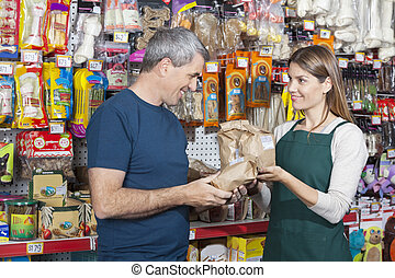 Saleswoman Assisting Man In Buying Pet Food - Smiling...
