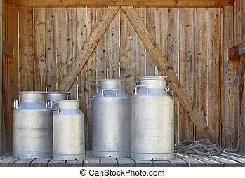 Metallic milk containers on a wooden background Farming...