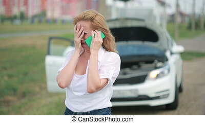 woman and broken car calling for help on cell phone. broken...