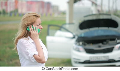 woman and broken car calling for help on cell phone broken...