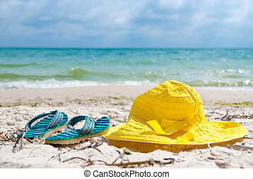 Hat and flip-flop - Yellow hat and blue flip-flop on a beach