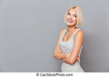 Cheerful attractive young woman standing with arms crossed...