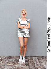 Full length of attractive young woman standing with arms...
