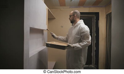 house painter with glasses and beard roller paints the wall....