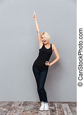 Happy successful young woman standing and pointing up over...