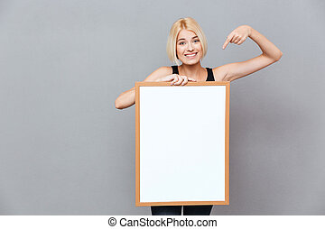 Smiling woman holding blank white board and pointing on it