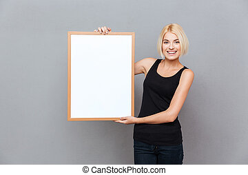 Happy pretty young woman holding blank white board