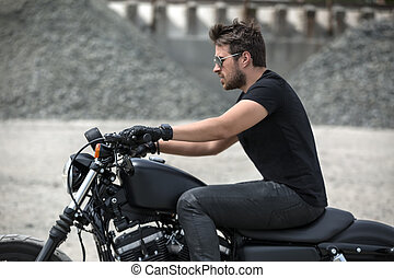 Bearded motorcyclist outdoors - Attractive man rides on the...